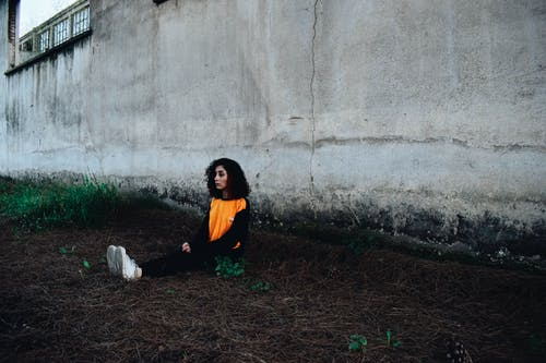 Young Woman Sitting Lonely on Ground under Dingy Wall of Industrial Building