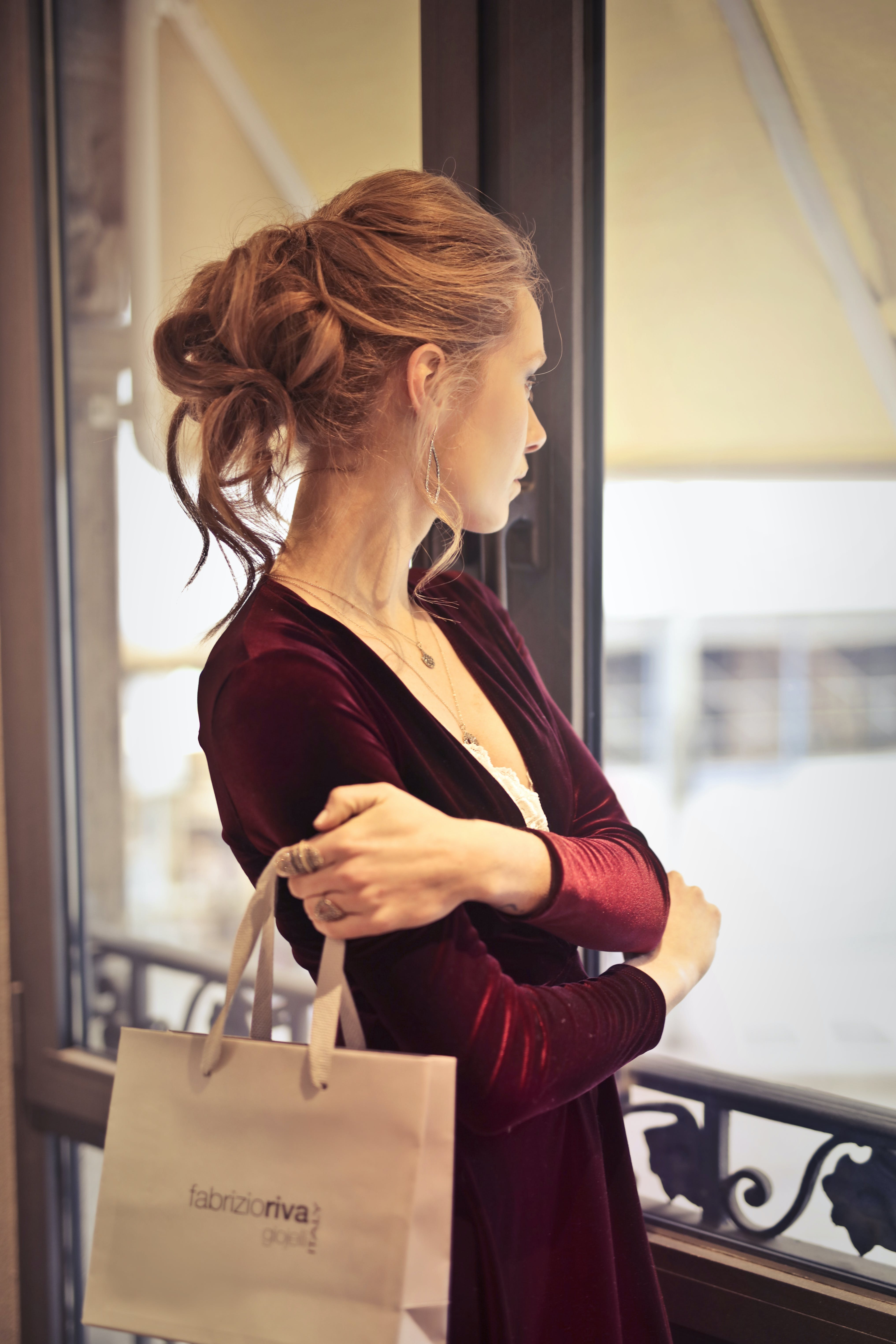Woman Holding White Paper Bag While Looking at the Window