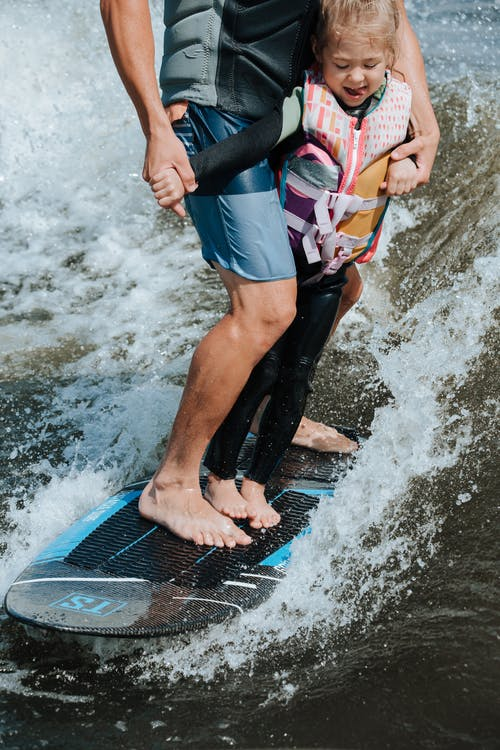 Close up on Father and Daughter on Wakesurf Board