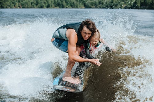 Father Holding Daughter on Wakesurf Board
