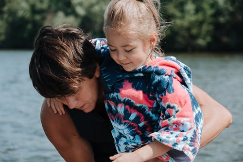 Daughter Hugging Father with Lake in Background