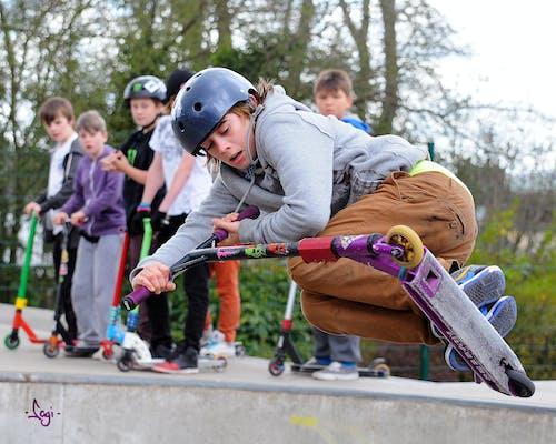 Foto stok gratis lad skuter di atas tepi mangkuk skate