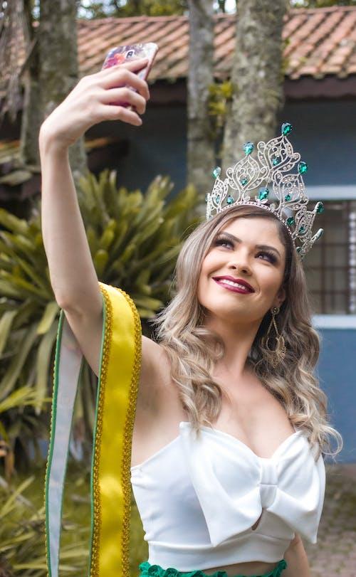 Woman in Crown Taking Selfie