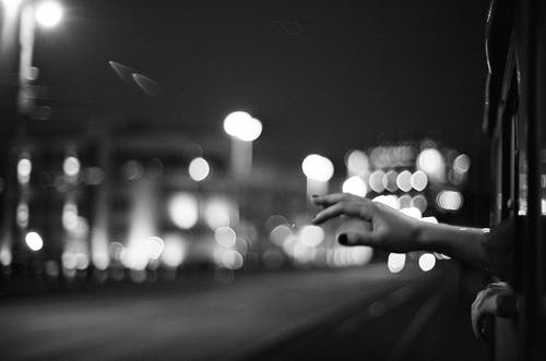 Black and White Picture of Hand Reaching Out from Train Window