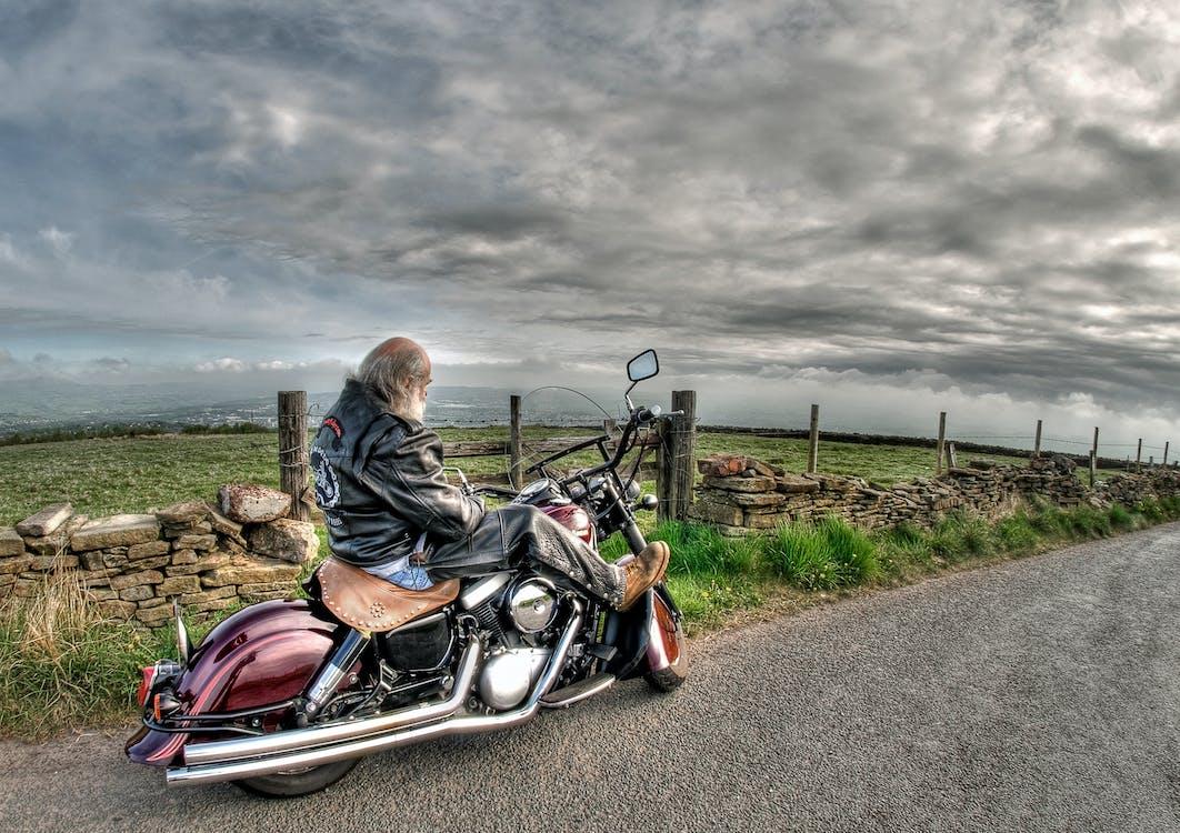Man Wearing Black Leather Jacket Riding Cruiser Motorcycle on Road