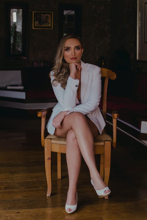 Portrait of Blonde Woman Sitting on Chair
