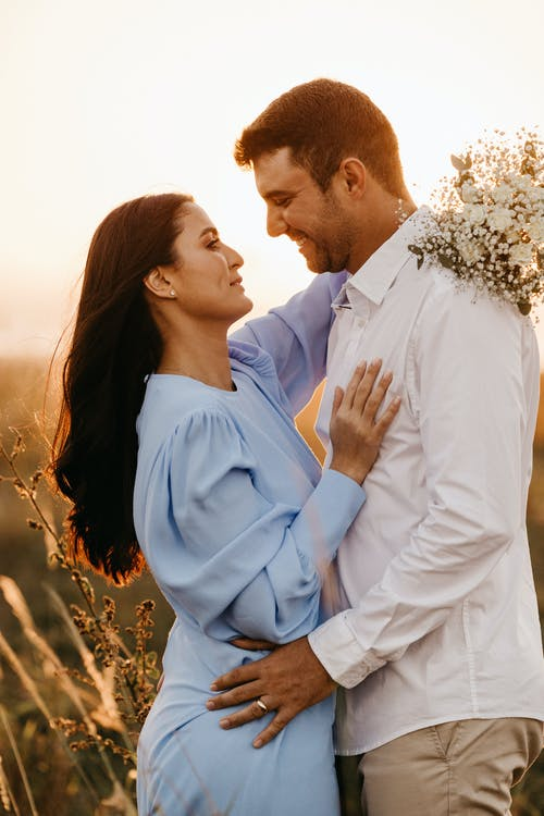 Man in White Dress Shirt Kissing Woman in Blue Dress