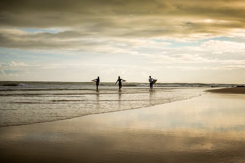 Rear View of Surfers on Beach