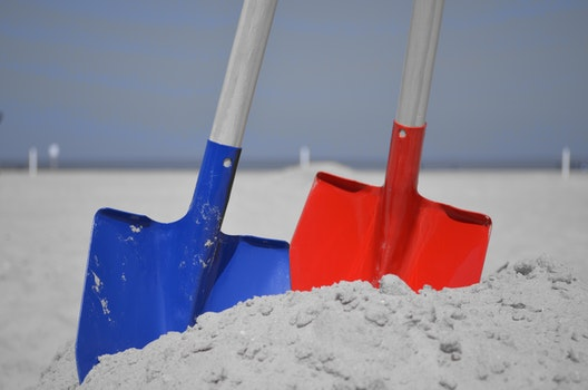 Blue and Red Shovel on Grey Sand during Daytime