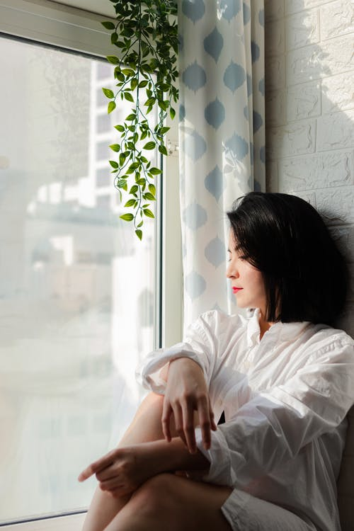Black-haired Woman Looking Through Window
