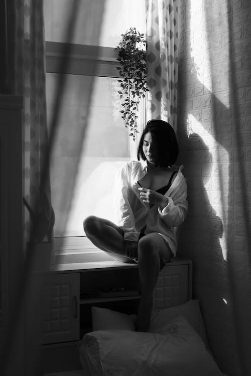 Woman Sitting on Windowsill