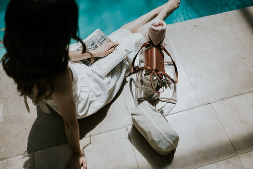 High Angle View of Sitting Woman Reading Book at Pool