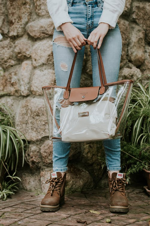 Woman in Jeans Holding Transparent Bag