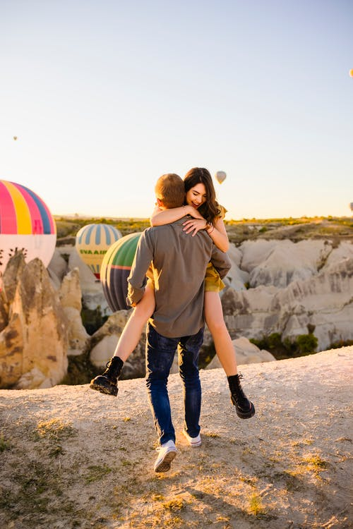 Man Holding Woman on His Hands Against Air Balloons