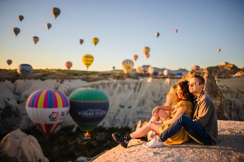 Couple Sitting on Stone and Watching Air Balloons