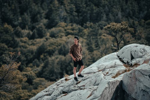 Man Posing on Rocks with Forest Below