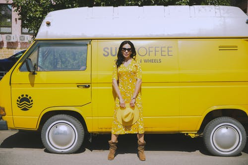 Woman in Yellow Dress Standing by Yellow Car