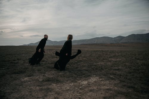 Portrait of Woman and Man in Black Cloths Walking on Grass