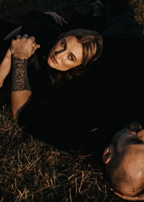 Couple Lying on Grass and Holding Hands