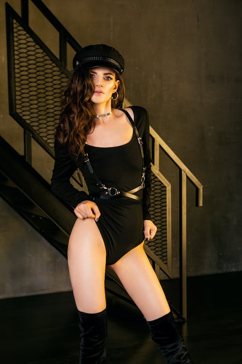 Woman in Boy Hat and Bodysuit Standing by Stairs