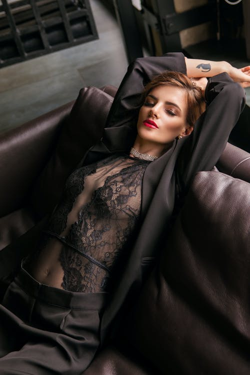 Woman in Lace Bodysuit and Black Suit on Leather Couch