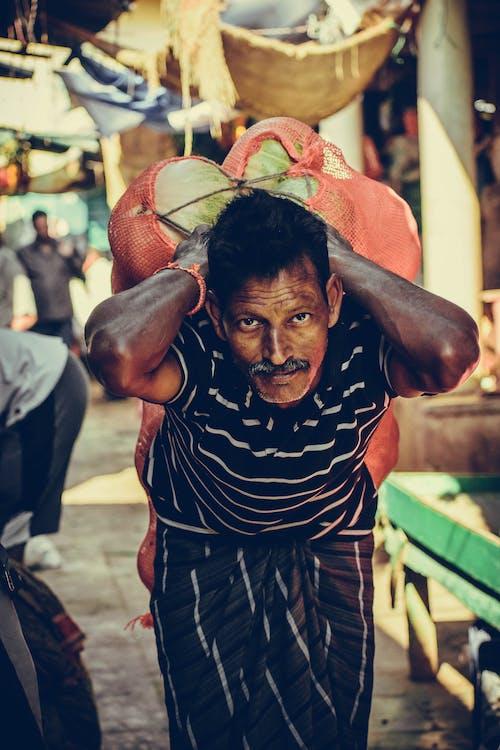 Porter Carrying Heavy Vegetables on Back at Bazaar