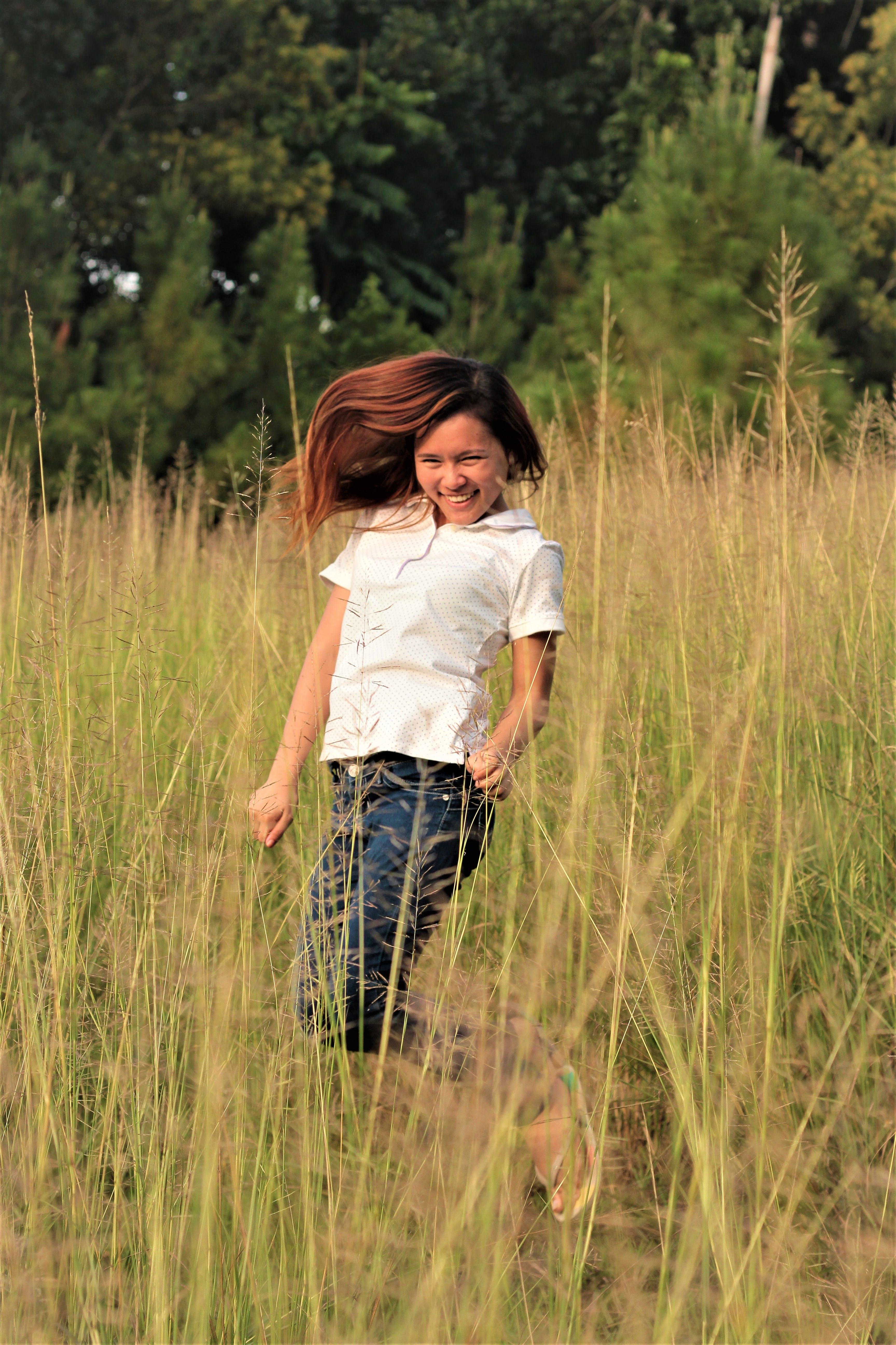 Woman Jumping Between Grass