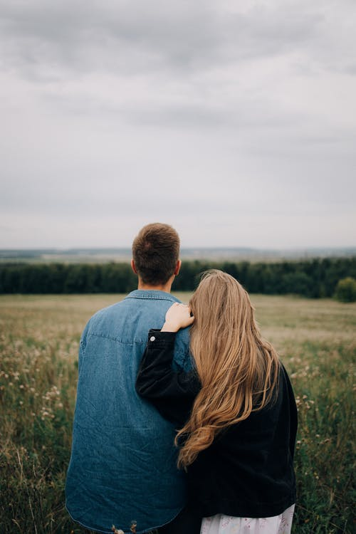 A Back View of Couple Looking at a Field