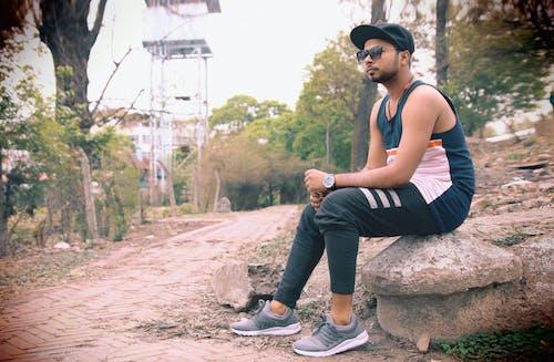 Man Wearing Black Tank Top Sitting on Gray Stone