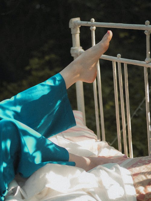 Female Legs Stretched Up in Bed Outdoors