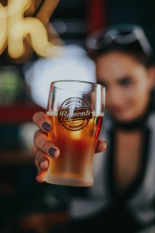 Close-up of Womans Hand Holding Glass of Beer