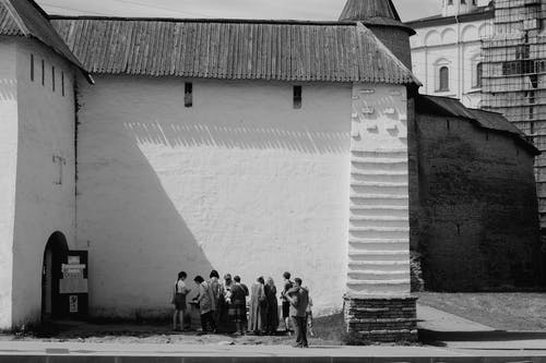 A Group of People Gathering Around an Entrance to an Old Building