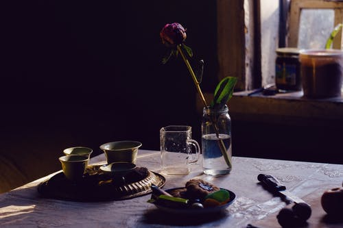 An Old Items on Table and a Single Rose in a Jar