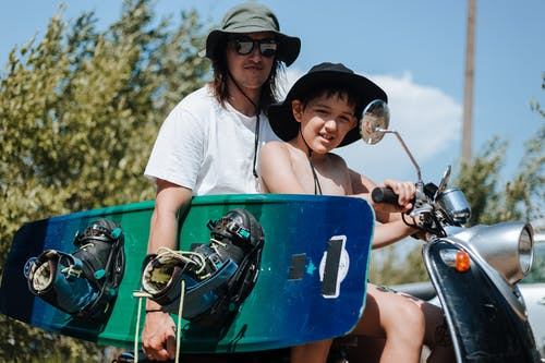 Father and Son Sitting on Scooter and Holding Wake Board