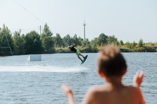 Son Watching His Father Doing Trick on Wake Board