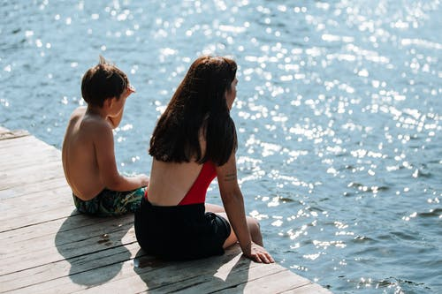 Son and Mother Sitting on Lake Pier