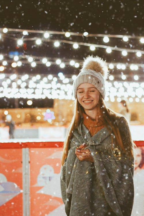 Teenage Girl in Winter Hat and Wrapped in Blanket with LED Lighting