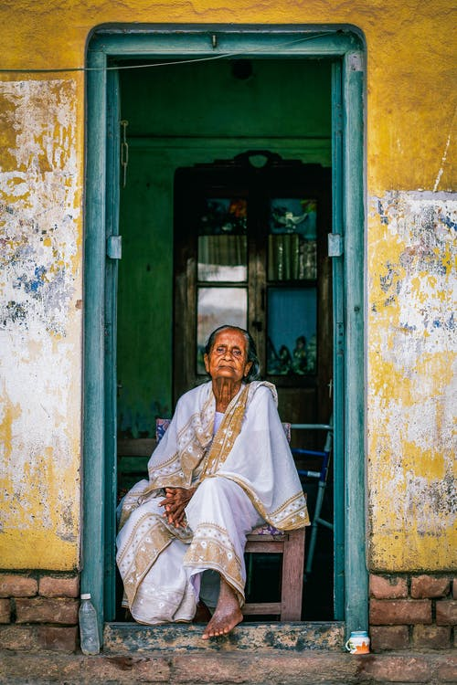 Portrait of Senior Woman Wearing Sari Sitting in Doorway