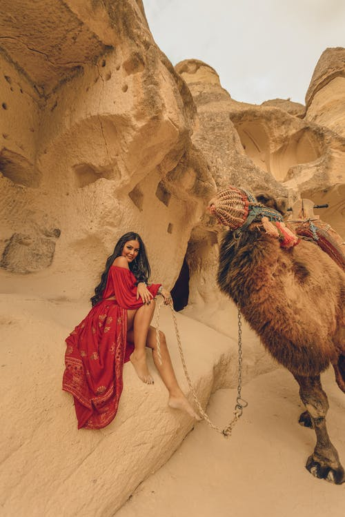Woman Sitting with Camel on Desert