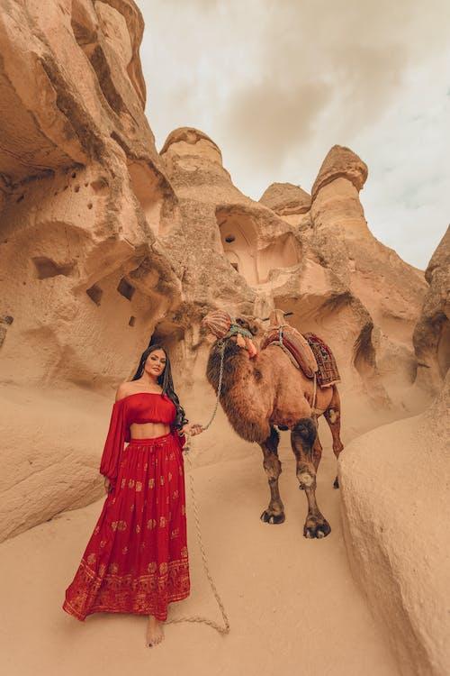Woman in Red Dress Holding Camel on Desert