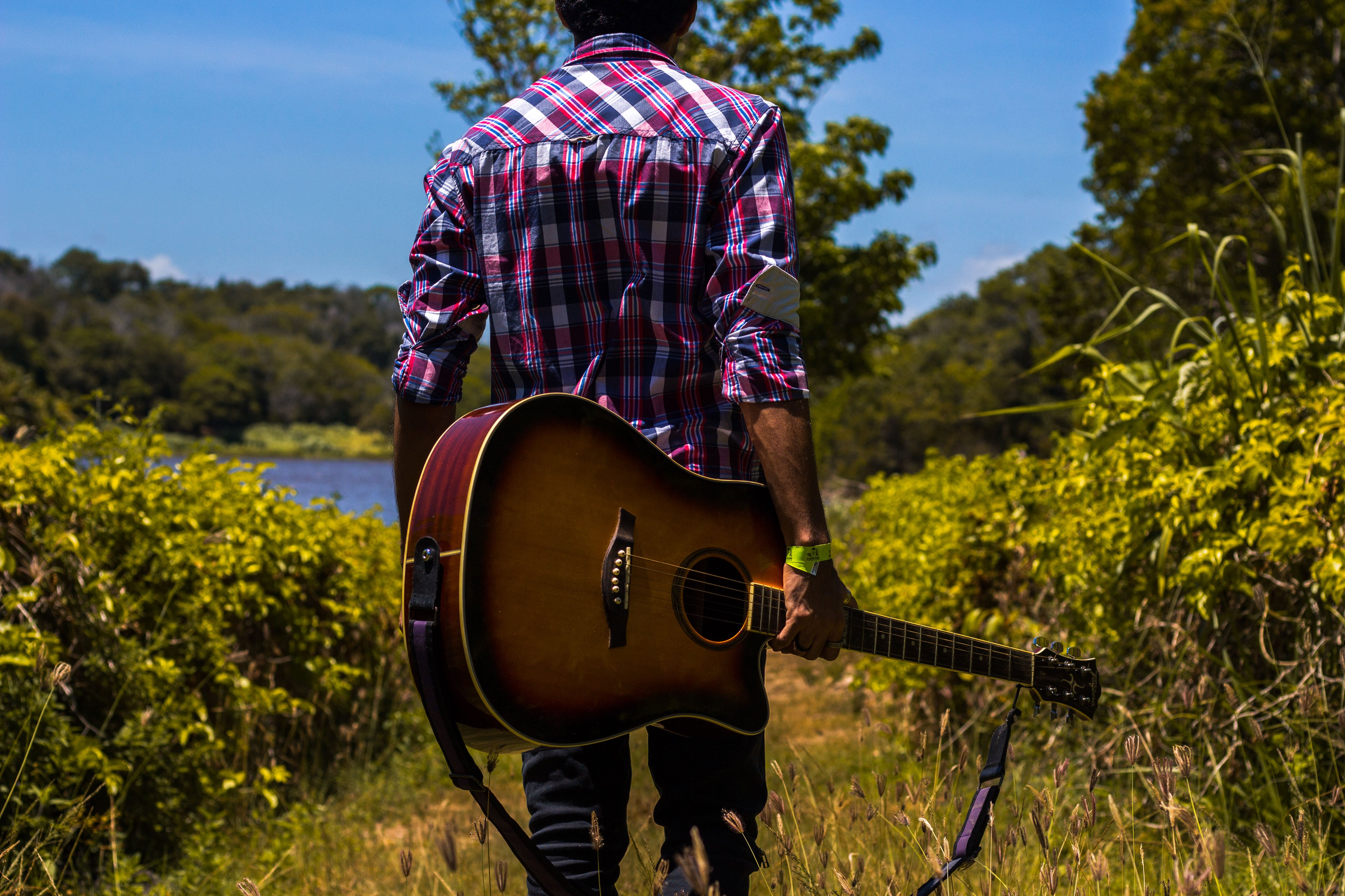 Man in Pink, Black, and White Plaid Dress Shirt Holding a Guitar Near Green Bush
