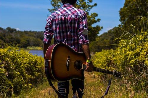 Man in Pink, Black, and White Plaid Dress Shirt Holding a Guitar Near Green Bush
