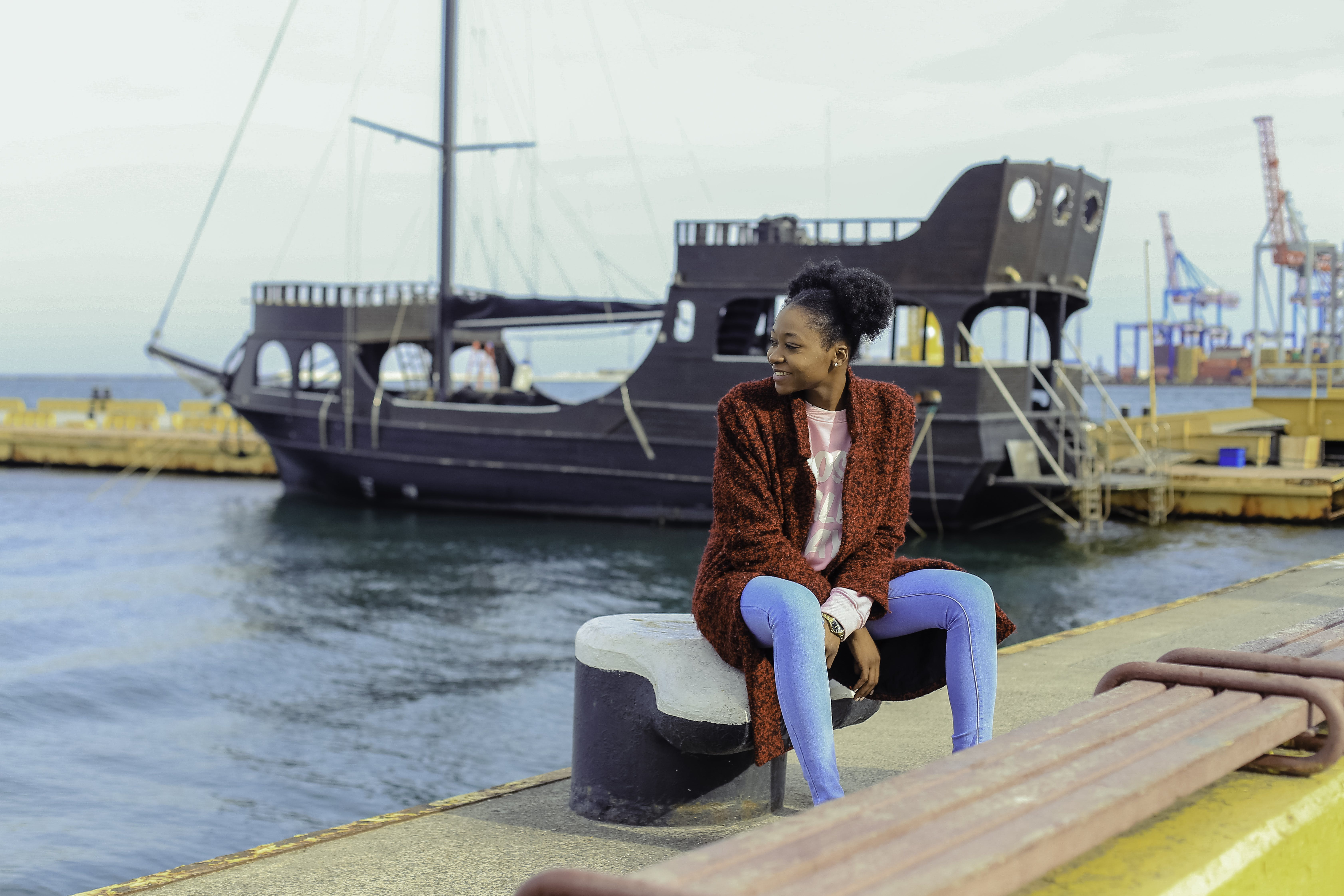Woman in Red Cardigan Sitting on Black Metal Near Boats