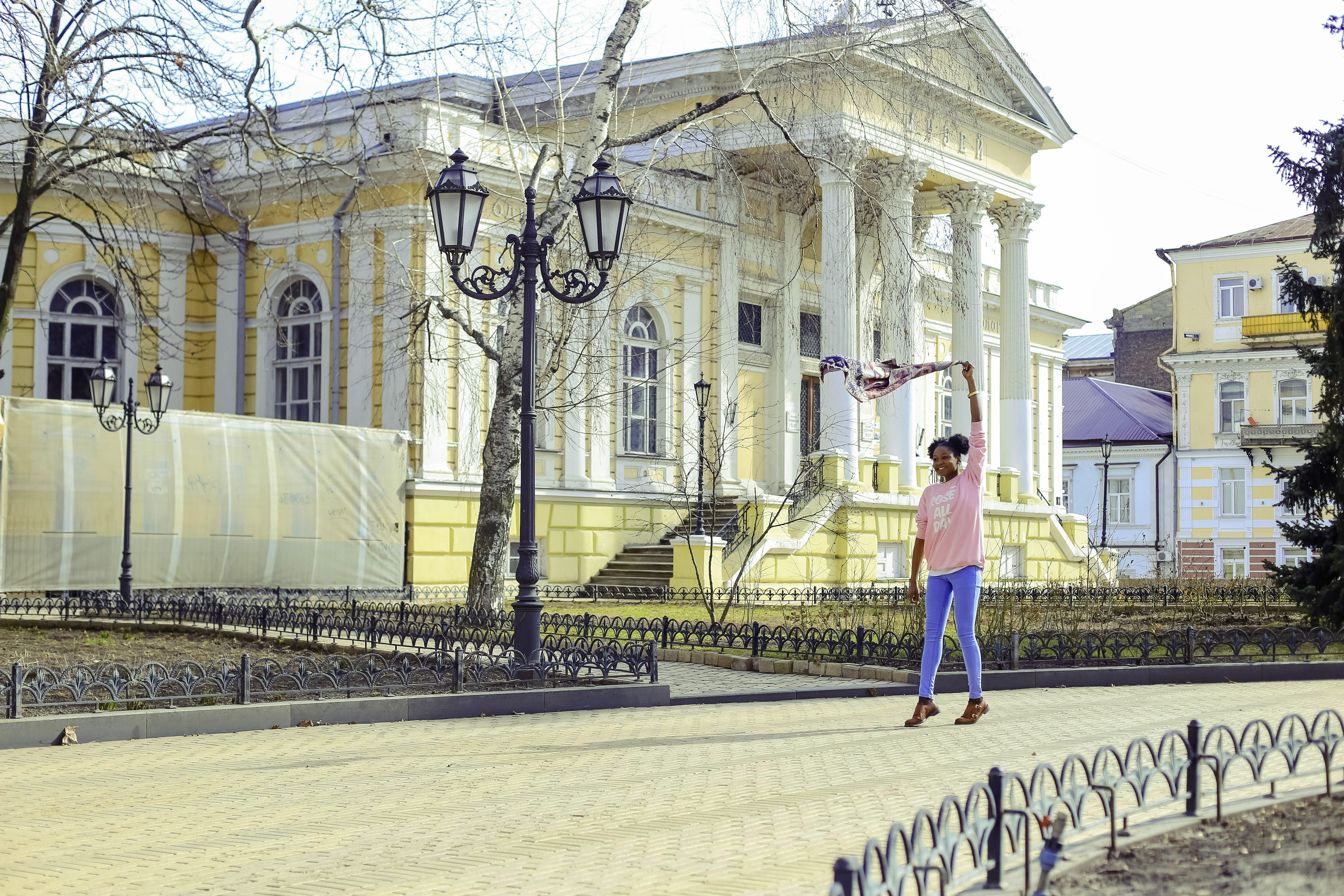 Girl Wearing Pink Long-sleeved Shirt and Blue Pants at Street
