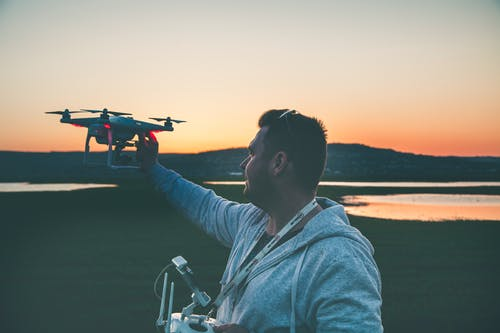 Man in Gray Jacket Holding Black Drone