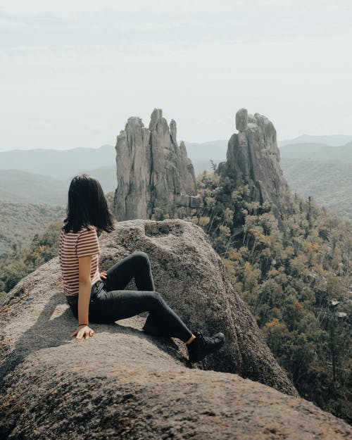 Woman Sitting on Rocks Edge