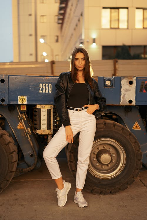 A Low Angle View on A Female Posing Over a Big Wheel Vehicle