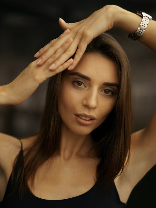 A Female Looking at Camera with Both Hands Connected on Her head