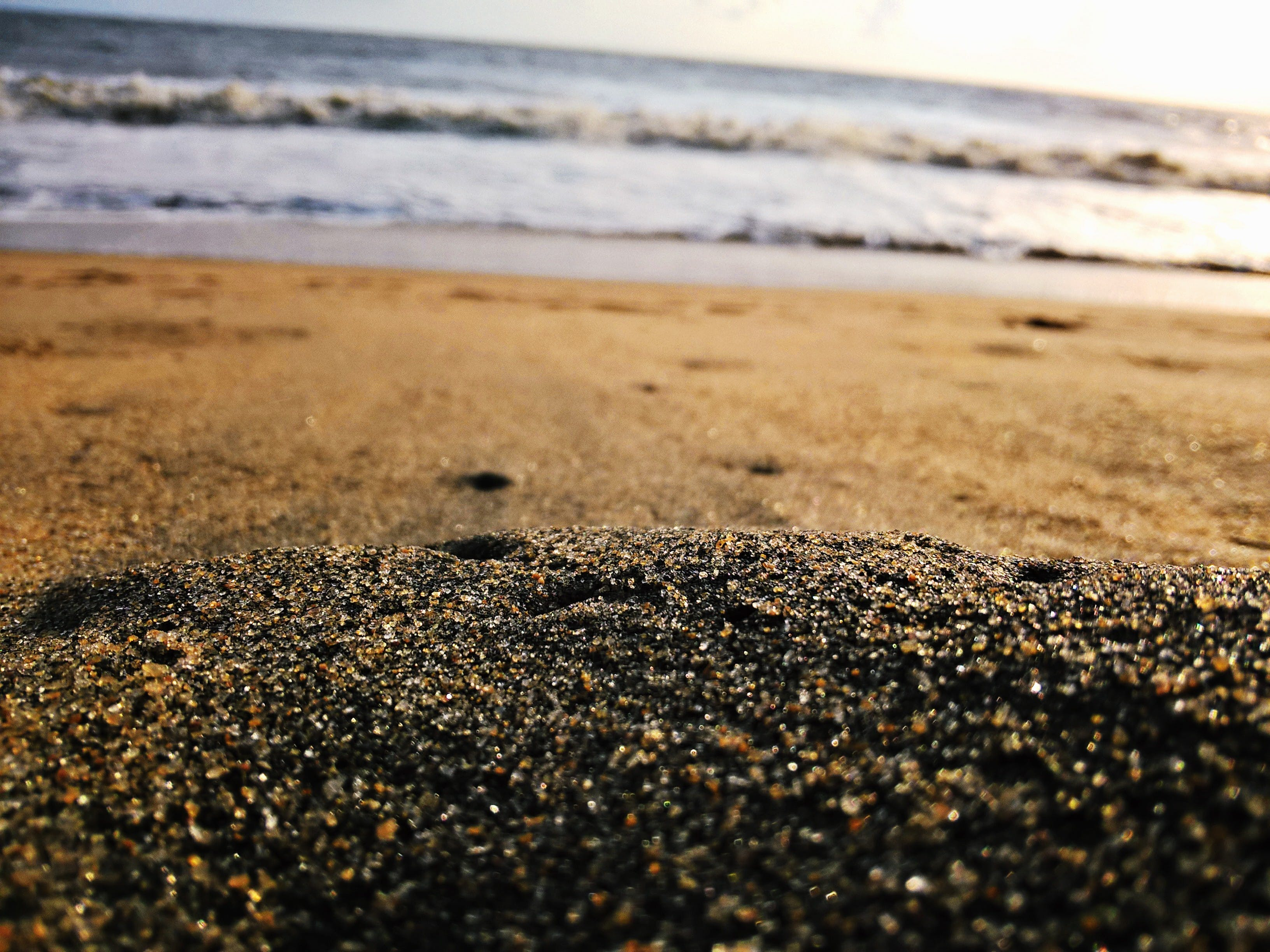 Low-angle Photography of Sand Near Body of Water