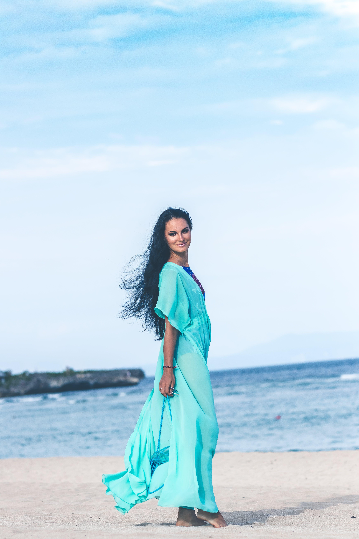 Woman in Teal Dress on Seashore